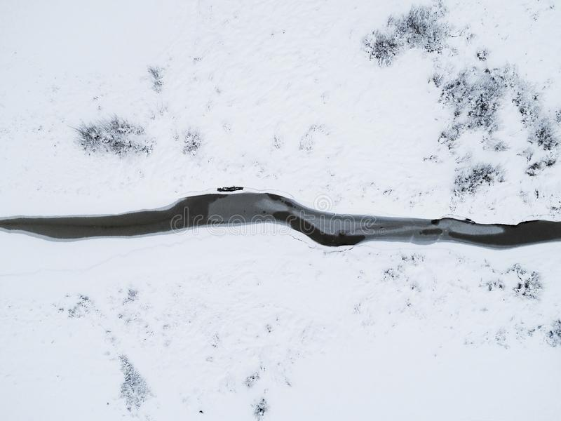 Aerial top view of frozen river among snow. Aerial winter landscape. Aerial winter. Aerial Snow texture. Beautiful snowy landscape. With river is covered ice royalty free stock photography