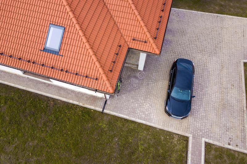 Aerial top view of house metal shingle roof with attic window and black car on paved yard royalty free stock photo