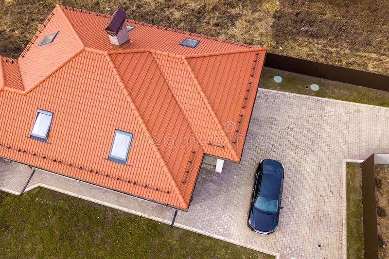 Aerial top view of house metal shingle roof with attic windows and black car on paved yard royalty free stock image