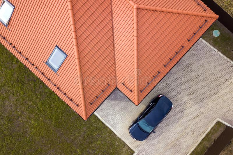 Aerial top view of house metal shingle roof with attic windows and black car on paved yard royalty free stock photography