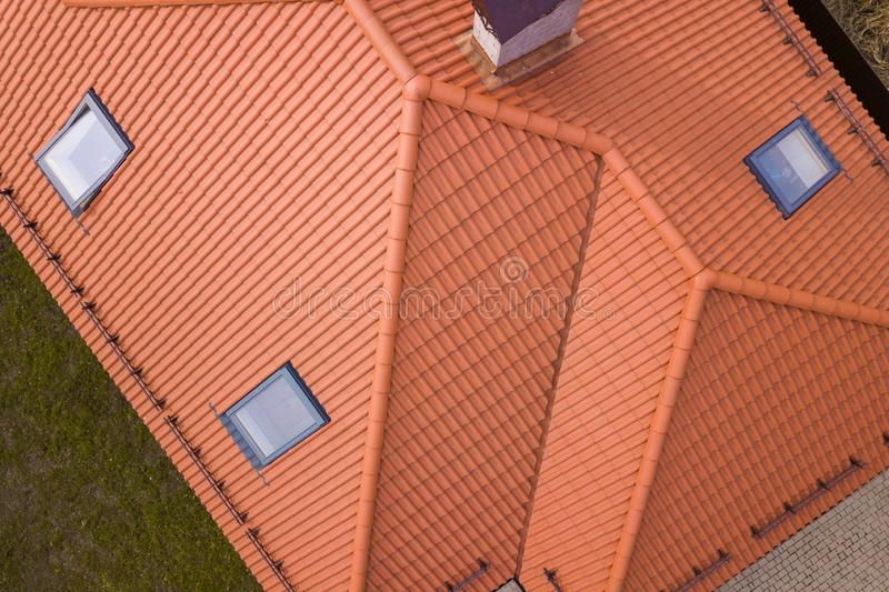 Aerial top view of house metal shingle roof, brick chimneys and small plastic attic windows. Roofing, repair and renovation work royalty free stock photos