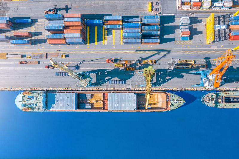 Aerial top view huge cargo ship moored at the pier at the port, loading goods, metal, concrete and other solid raw materials stock photos
