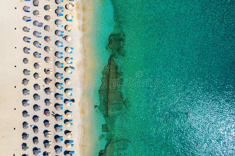 Aerial top view of Kalafatis beach on Mykonos island, Greece. With emerald sea, umbrellas, sunchairs and fine sand royalty free stock photos