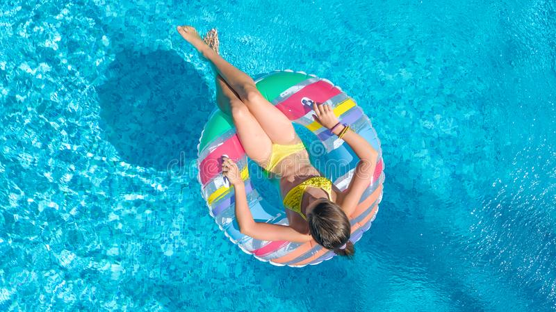 Aerial top view of little girl in swimming pool from above, kid swims on inflatable ring donut , child has fun in water. On family vacation resort stock image