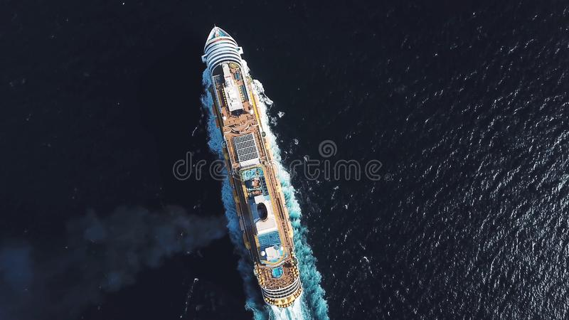 Aerial top view of luxury large cruise ship sailing full speed on open water, luxury vacation concept. Stock. Large stock images