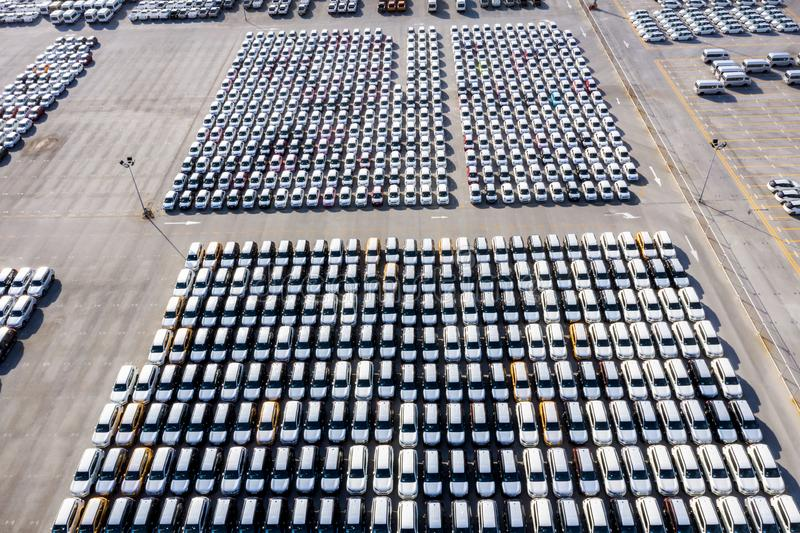 Aerial top view new cars lined up in the port for import export business logistic and transportation by ship in the open sea. New stock photos