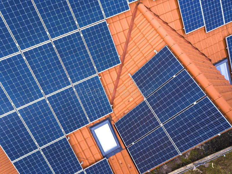 Aerial top view of new modern residential house cottage with blue shiny solar photo voltaic panels system on roof. Renewable stock photo