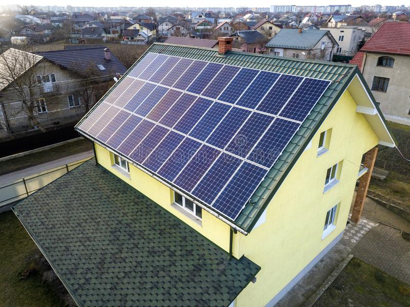 Aerial top view of new modern residential house cottage with blue shiny solar photo voltaic panels system on roof. Renewable stock images