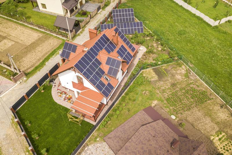 Aerial top view of new modern residential house cottage with blue shiny solar photo voltaic panels system on roof. Renewable. Ecological green energy production stock photo
