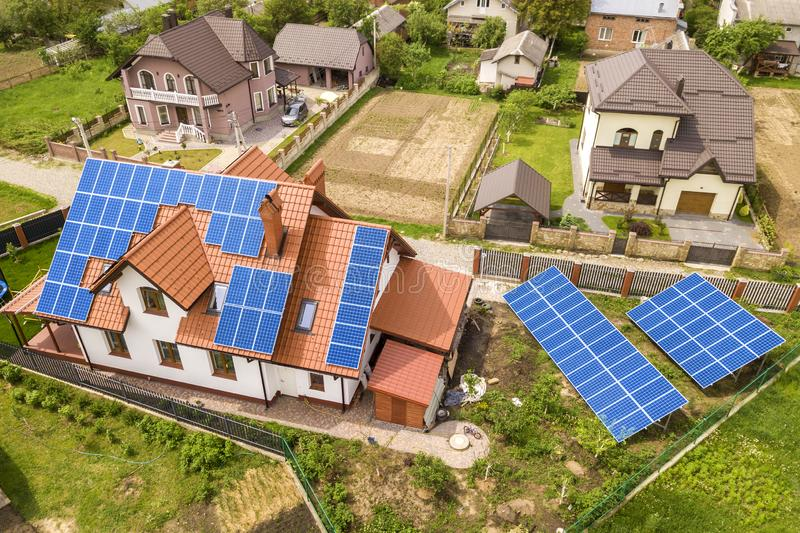 Aerial top view of new modern residential house cottage with blue shiny solar photo voltaic panels system on roof. Renewable. Ecological green energy production stock images