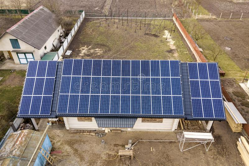 Aerial top view of new modern residential house cottage with blue shiny solar photo voltaic panels system on roof. Renewable. Ecological green energy production stock image