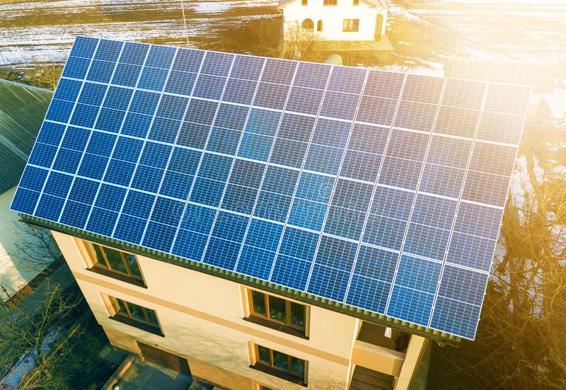Aerial top view of new modern residential two story house cottage with blue shiny solar photo voltaic panels system on roof. Renewable ecological green energy stock photo