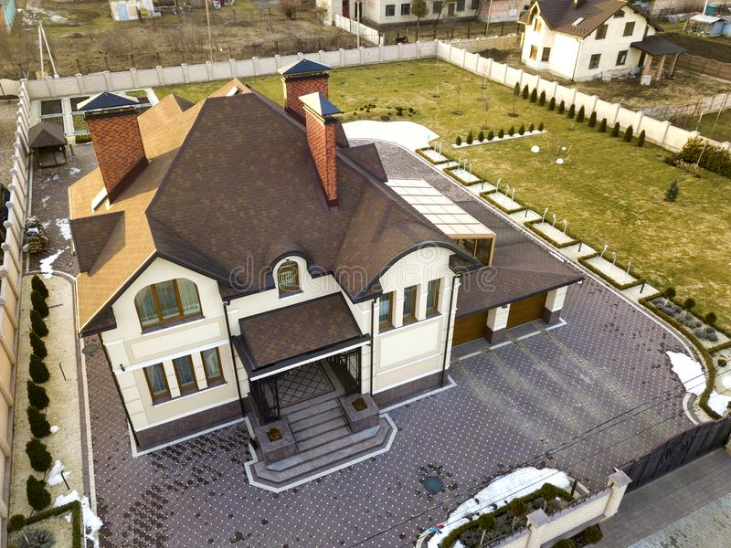 Aerial top view of new residential house cottage with shingle roof on fenced big yard on sunny day stock photo