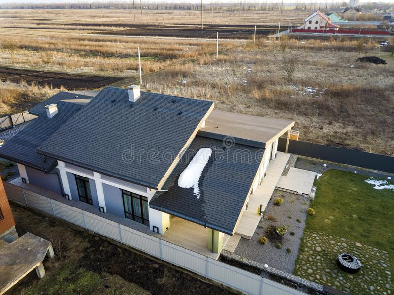 Aerial top view of new residential house cottage and terrace with shingle roof on fenced big yard on sunny winter day royalty free stock photos