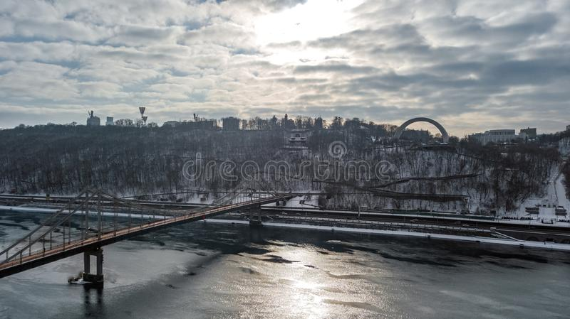 Aerial top view of pedestrian Park bridge in winter and Dnieper river from above, snow Kyiv cityscape, city of Kiev skyline stock images