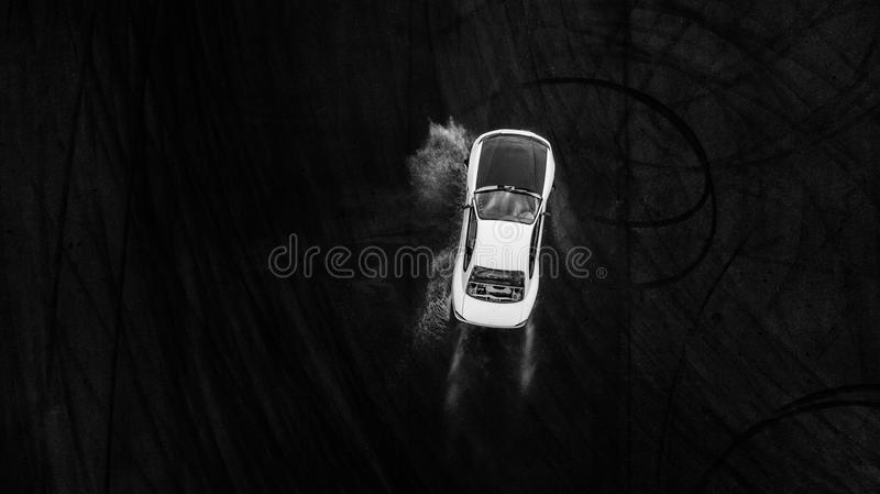 Aerial top view professional driver drifting car on wet race track, with water splash. stock image