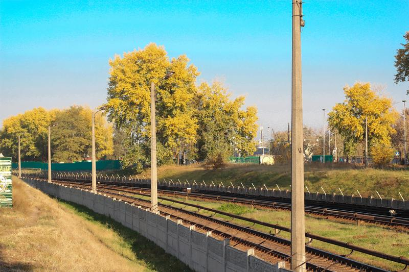 Aerial top view on railway road between trees. Forest landscape background with steel rails. power transmission lines support stock photography