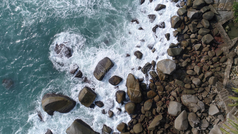 Aerial top view of sea waves hitting rocks on the beach in Phuket royalty free stock photos