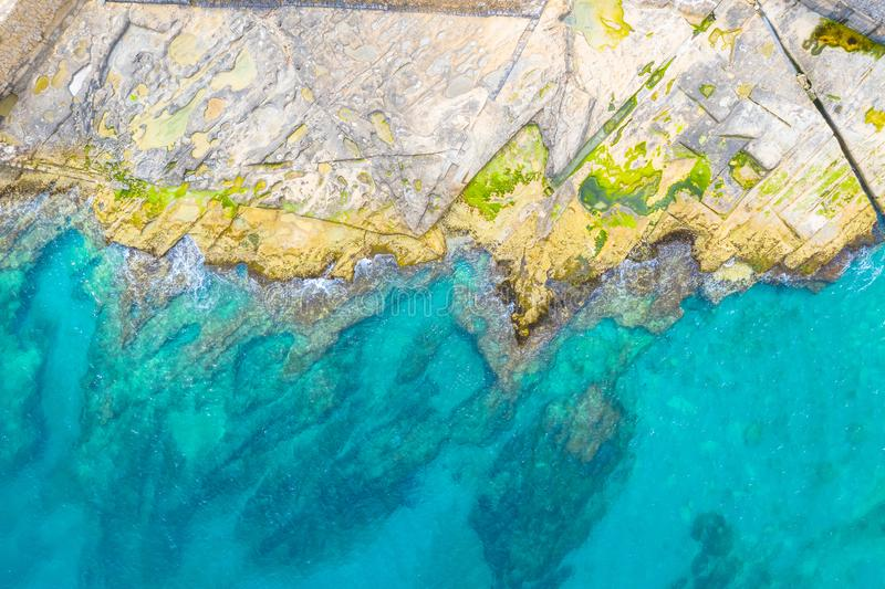 Aerial top view of sea waves hitting rocks on the rocky beach with green algae with turquoise sea water. Seascape in the coastline stock photo