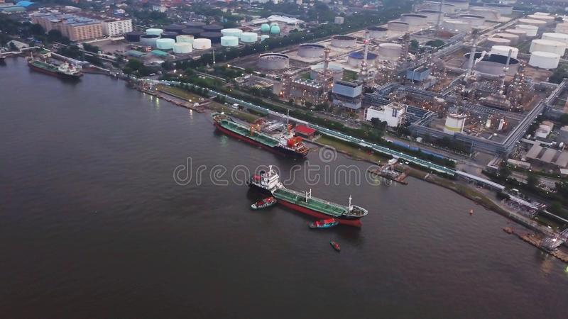 Aerial top view of ships in front of Petroleum`s oil refinery in. Industrial engineering and transportation concept. Oil and gas tanks industry. Modern factory stock image
