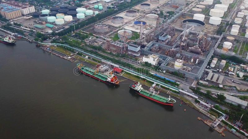 Aerial top view of ships in front of Petroleum`s oil refinery in. Industrial engineering and transportation concept. Oil and gas tanks industry. Modern factory royalty free stock photos