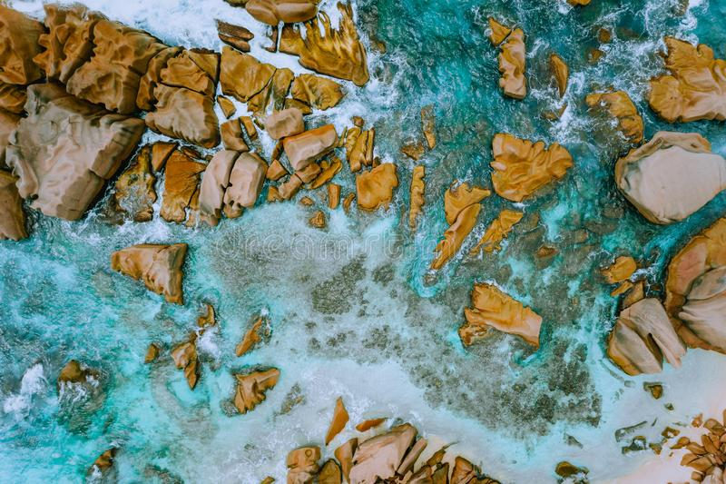 Aerial top view of tropical coastline. Bizarre granite rocks boulders, turquoise azure water. Amazing shore seascape stock photos