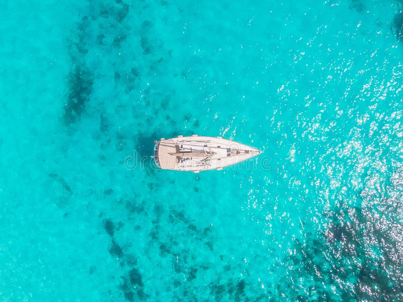 Aerial top view white yacht with sail stands on coral reef in blue transparent turquoise sea. Concept travel.  stock image