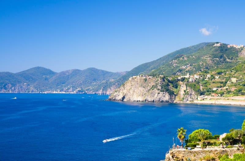 Aerial top view of white yacht sail on water of Ligurian Sea near coastline of Riviera di Levante, National park Cinque Terre Coas. T, Corniglia village on rock royalty free stock photos