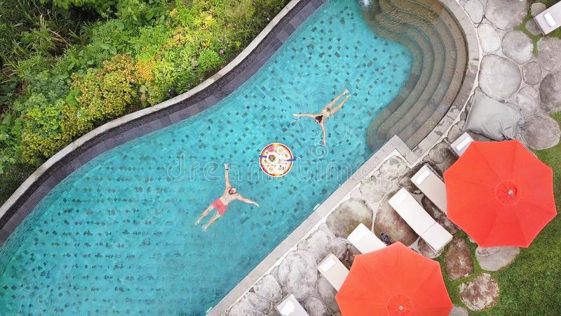 Aerial Top View: Young Couple with Floating Breakfast in Swimming Pool. Man and Woman Swim Towards Each Other. Tropical Vacation royalty free stock image