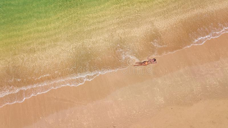 Aerial top view of young woman in bikini relaxing on sand tropical beach by sea and waves from above, girl on tropical island. Beach vacation in Thailand stock photography