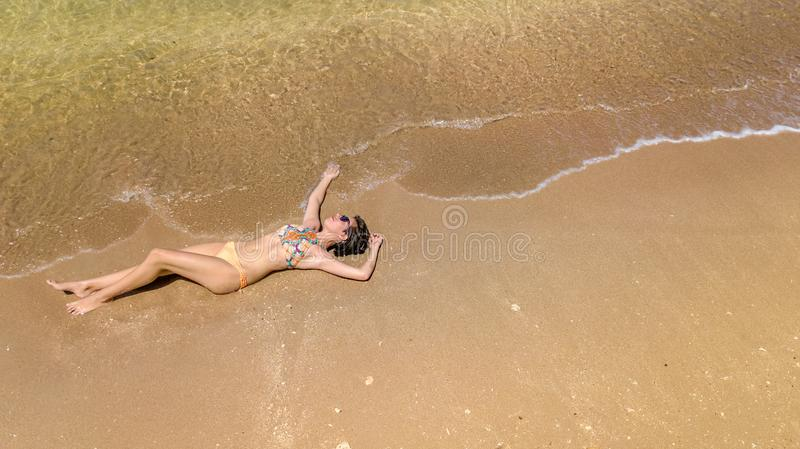 Aerial top view of young woman in bikini relaxing on sand tropical beach by sea and waves from above, girl on tropical island stock image