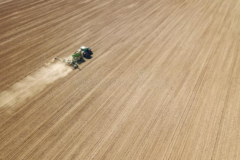Aerial Tractor sowing crops at field. Food industry stock image
