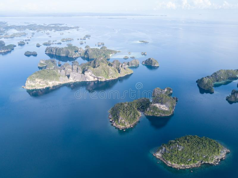 Aerial of Tropical Islands in Raja Ampat. The limestone islands found in Raja Ampat are surrounded by healthy coral reefs. This beautiful, tropical region in royalty free stock image
