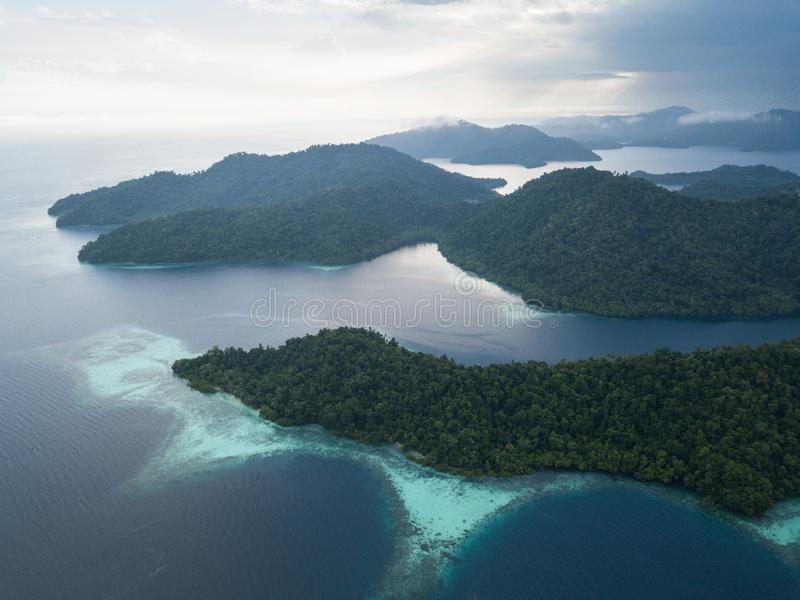 Aerial of Tropical Islands and Reefs in Raja Ampat. The beautiful islands found throughout Raja Ampat, Indonesia, are surrounded by healthy coral reefs. This royalty free stock photo