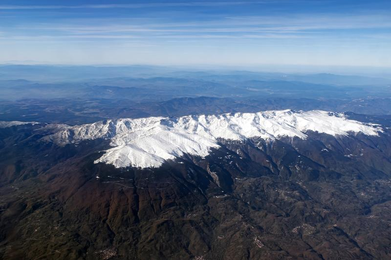 Aerial veiw of a dale with white mountian peaks, misty horizon line and skyscape. Scenic view from window of a flight passing royalty free stock images