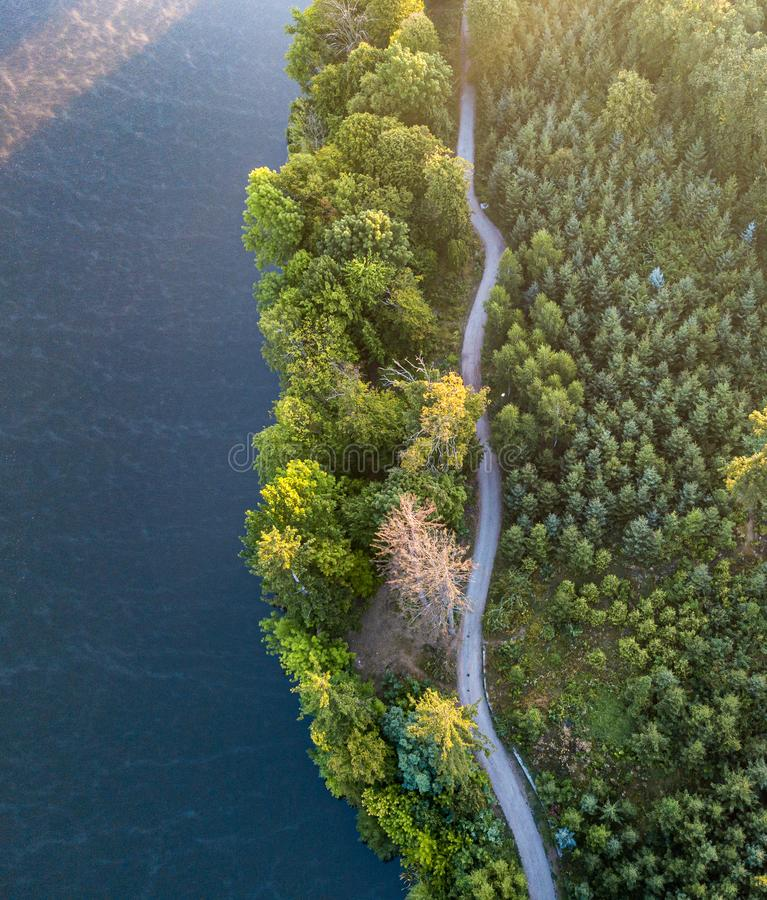 Aerial veiw of empty road in green forest with the blue lake. drone shot. Aerial veiw of empty road in green forest with the blue lake stock photo