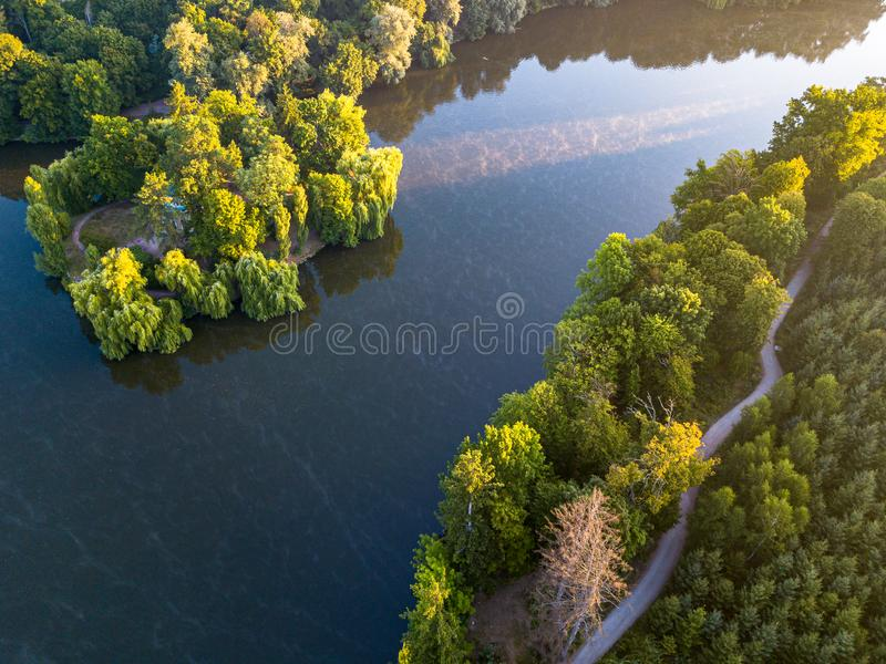 Aerial veiw of empty road in green forest with the blue lake. drone shot. Aerial veiw of empty road in green forest with the blue lake stock image