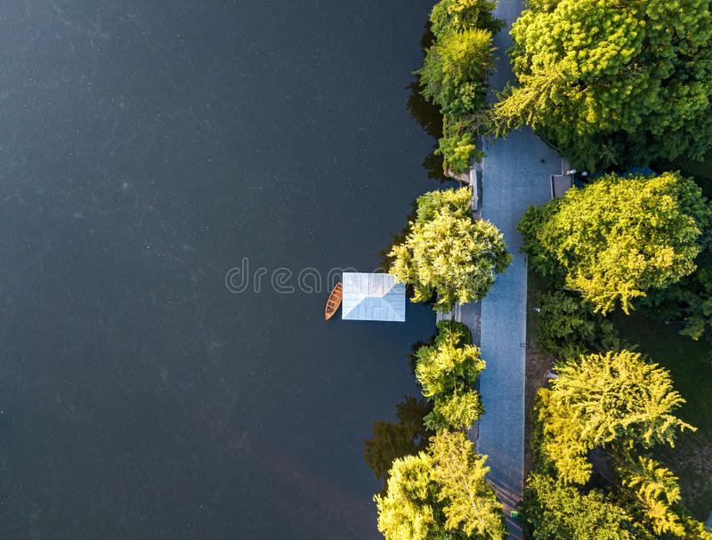 Aerial veiw of empty road in green forest with the blue lake. drone shot. Aerial veiw of empty road in green forest with the blue lake stock images