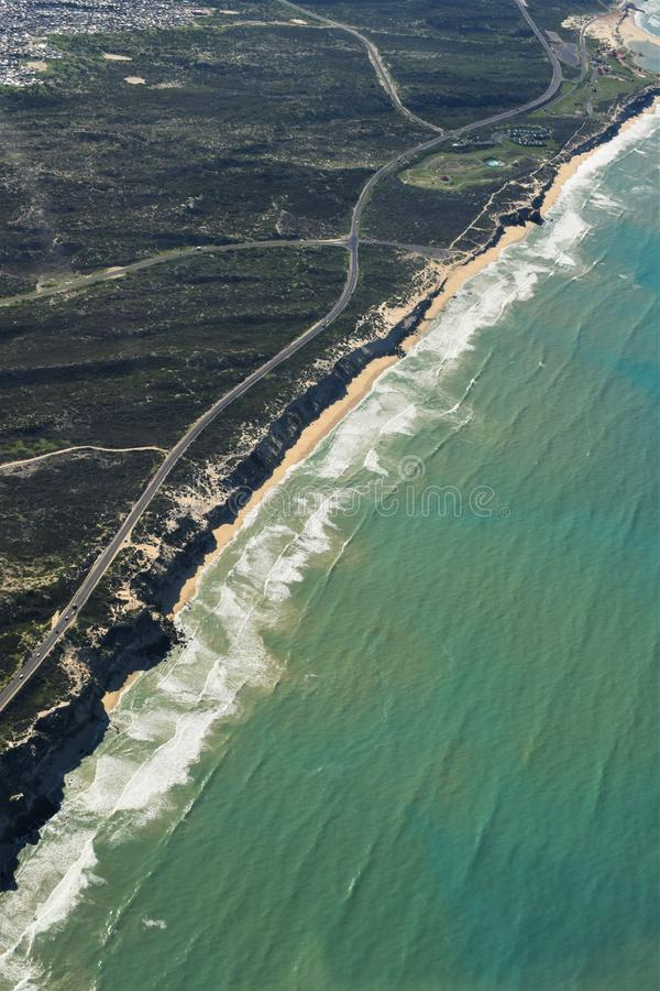 Aerial vertical shot of a road in the middle of grassy fields near a beach shore stock image