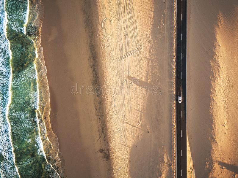 Aerial vertical view of yellow tropical sandy beach with black long way road and car traveling - ocean blue waves and shore - royalty free stock image