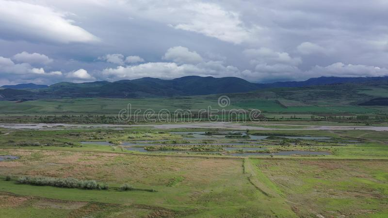 Aerial . Green fields and river. Mountains are visible on the horizon. Overcast sky. Animals can be seen near the river royalty free stock photo