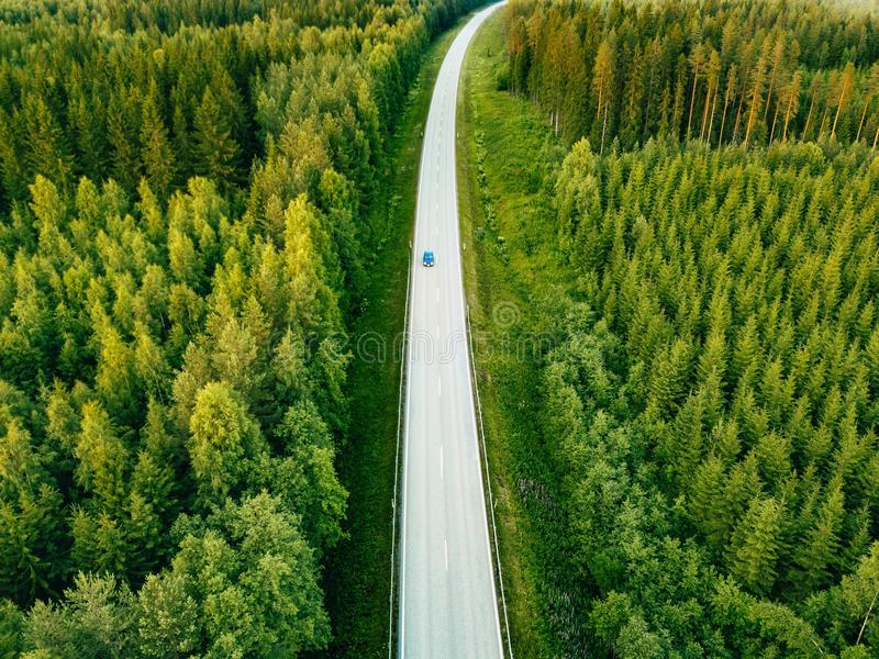 Aerial view from above of country road through the green summer forest in summer Finland. royalty free stock photo