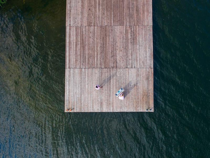 Aerial view from above of two girls singing at the old pier. Surrealism stock photo