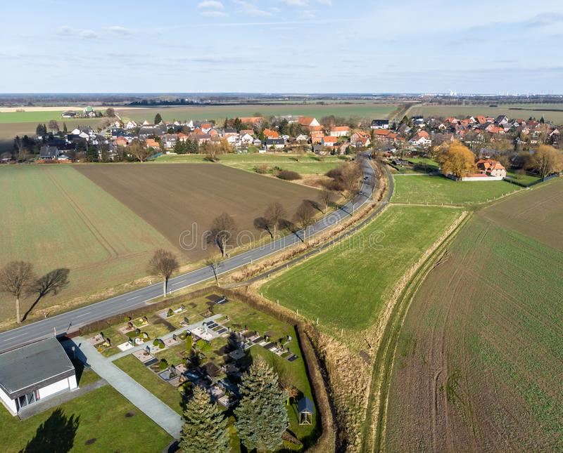 Aerial view of the access and transit road to a small village near Wolfsburg. With the village cemetery in the front corner of the royalty free stock photos