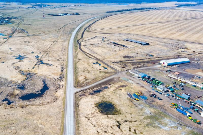 Aerial view on agricultural machinery near the hangar in the village for planting and harvesting. Agriculture and farming with the. Road going into the distance royalty free stock images
