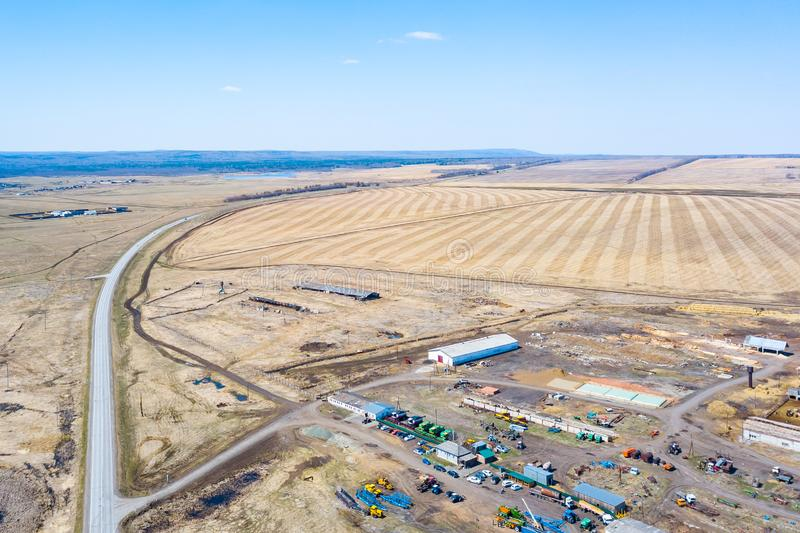 Aerial view on agricultural machinery near the hangar in the village for planting and harvesting. Agriculture and farming with the. Road going into the distance royalty free stock photos
