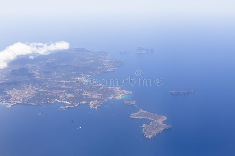Aerial view from the airplane of Ibiza island with blue beautiful water. Clouds. Holidays and summer concept. Pleasure, seascape, scenic, destinations, green stock image