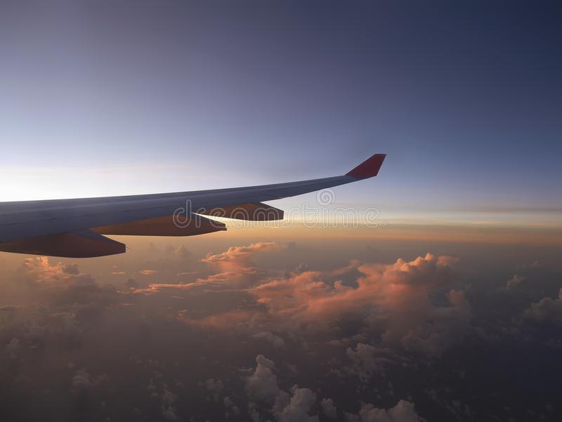 Aerial view from airplane, seeing plane`s wing and pink sunset light from left side. Over clouds horizon under blue sky which is getting dark stock photography