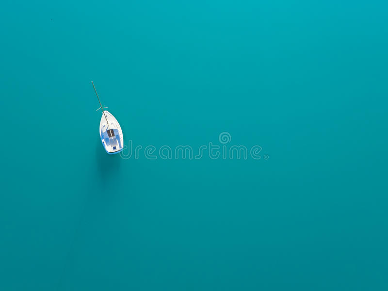 Aerial view of alone yacht sailling on azure water royalty free stock photography