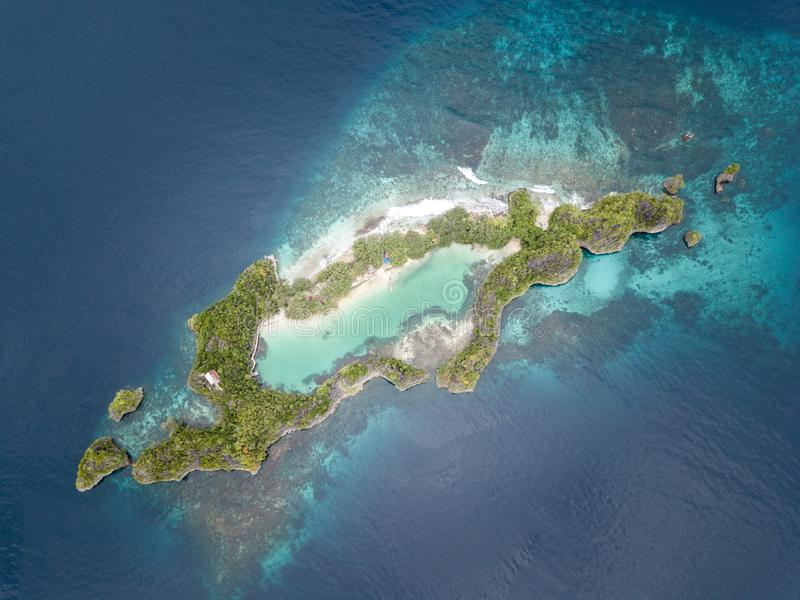 Aerial View of Amazing Limestone Islands in Raja Ampat. A beautiful set of limestone islands is surrounded by a healthy coral reef in Raja Ampat, Indonesia. This stock image